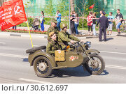 Купить «Russia, Samara, May 9, 2018: Motorcyclists in the form of the period of the Great Patriotic War on an army heavy motorcycle M-72 with a DP machine gun at a parade in Samara.», фото № 30612697, снято 9 мая 2018 г. (c) Акиньшин Владимир / Фотобанк Лори