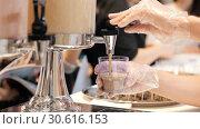 Купить «A person working in the buffet. Pouring a drink in the cup for degustation», видеоролик № 30616153, снято 29 марта 2020 г. (c) Константин Шишкин / Фотобанк Лори