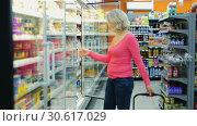 Portrait of mature woman choosing fresh dairy products on shelves in grocery shop. Стоковое видео, видеограф Яков Филимонов / Фотобанк Лори