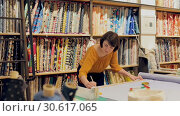 Купить «Experienced saleswoman arranging fabric bolts in textile shop, preparing for sale», видеоролик № 30617065, снято 22 февраля 2019 г. (c) Яков Филимонов / Фотобанк Лори