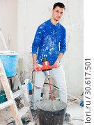 Купить «Male builder mixing plaster using electric mixer», фото № 30617501, снято 21 мая 2017 г. (c) Яков Филимонов / Фотобанк Лори