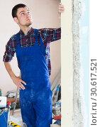 Builder handyman examining room and planning renovation. Стоковое фото, фотограф Яков Филимонов / Фотобанк Лори