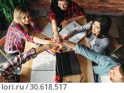 Купить «Group of students clasped hands over the table», фото № 30618517, снято 3 марта 2019 г. (c) Tryapitsyn Sergiy / Фотобанк Лори
