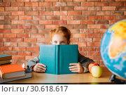 Купить «Cute schoolgirl with textbooks poses at the table», фото № 30618617, снято 7 апреля 2019 г. (c) Tryapitsyn Sergiy / Фотобанк Лори