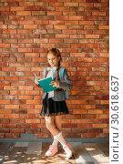 Купить «Cute schoolgirl with schoolbag reading a textbook», фото № 30618637, снято 7 апреля 2019 г. (c) Tryapitsyn Sergiy / Фотобанк Лори