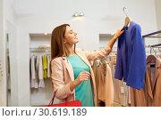 Купить «happy woman choosing clothes at clothing store», фото № 30619189, снято 19 февраля 2016 г. (c) Syda Productions / Фотобанк Лори
