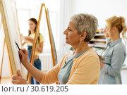 Купить «senior woman drawing on easel at art school studio», фото № 30619205, снято 26 мая 2017 г. (c) Syda Productions / Фотобанк Лори