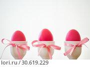 Купить «pink easter eggs in holders on white background», фото № 30619229, снято 15 марта 2018 г. (c) Syda Productions / Фотобанк Лори