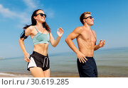 Купить «couple with phones and arm bands running on beach», фото № 30619285, снято 1 августа 2018 г. (c) Syda Productions / Фотобанк Лори