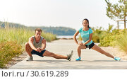 smiling couple stretching legs on beach. Стоковое фото, фотограф Syda Productions / Фотобанк Лори