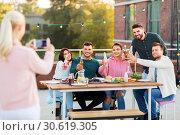 Купить «happy friends photographing at rooftop party», фото № 30619305, снято 2 сентября 2018 г. (c) Syda Productions / Фотобанк Лори