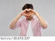 Купить «man making hand heart gesture over grey background», фото № 30619337, снято 3 февраля 2019 г. (c) Syda Productions / Фотобанк Лори