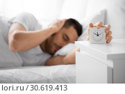 Купить «close up of man in bed reaching for alarm clock», фото № 30619413, снято 6 мая 2017 г. (c) Syda Productions / Фотобанк Лори