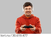 Купить «man with gamepad playing video game», фото № 30619477, снято 3 февраля 2019 г. (c) Syda Productions / Фотобанк Лори
