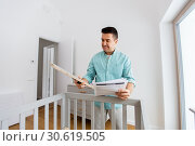 Купить «father with manual assembling baby bed at home», фото № 30619505, снято 10 февраля 2019 г. (c) Syda Productions / Фотобанк Лори