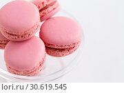 Купить «close up of pink macarons on confectionery stand», фото № 30619545, снято 6 июля 2018 г. (c) Syda Productions / Фотобанк Лори