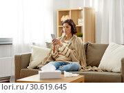 Купить «sad sick woman in blanket using smartphone at home», фото № 30619645, снято 6 марта 2019 г. (c) Syda Productions / Фотобанк Лори