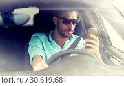 Купить «man in sunglasses driving car with smartphone», фото № 30619681, снято 12 июня 2016 г. (c) Syda Productions / Фотобанк Лори