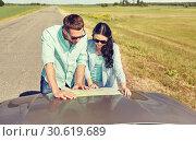 Купить «happy man and woman with road map on car hood», фото № 30619689, снято 12 июня 2016 г. (c) Syda Productions / Фотобанк Лори