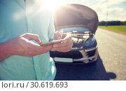Купить «close up of man with smartphone and broken car», фото № 30619693, снято 12 июня 2016 г. (c) Syda Productions / Фотобанк Лори