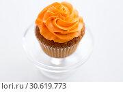Купить «cupcake with frosting on confectionery stand», фото № 30619773, снято 6 июля 2018 г. (c) Syda Productions / Фотобанк Лори