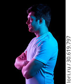 Купить «man with crossed arms over neon lights in darkness», фото № 30619797, снято 3 февраля 2019 г. (c) Syda Productions / Фотобанк Лори