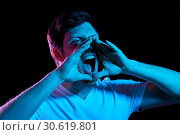 Купить «angry man screaming over neon lights in dark room», фото № 30619801, снято 3 февраля 2019 г. (c) Syda Productions / Фотобанк Лори