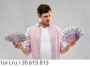 Купить «uncertainy man with fans of euro and dollar money», фото № 30619813, снято 3 февраля 2019 г. (c) Syda Productions / Фотобанк Лори