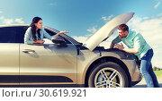 Купить «couple with open hood of broken car at countryside», фото № 30619921, снято 12 июня 2016 г. (c) Syda Productions / Фотобанк Лори