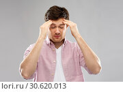 unhappy young man suffering from headache. Стоковое фото, фотограф Syda Productions / Фотобанк Лори