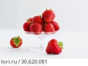 Купить «strawberries on glass stand over white background», фото № 30620081, снято 6 июля 2018 г. (c) Syda Productions / Фотобанк Лори