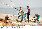 Купить «happy friends with fishing rods on pier», фото № 30620093, снято 8 сентября 2018 г. (c) Syda Productions / Фотобанк Лори
