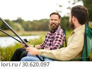 Купить «happy friends with fishing rods on lake», фото № 30620097, снято 8 сентября 2018 г. (c) Syda Productions / Фотобанк Лори