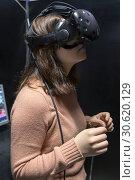Купить «Enthusiastic glad positive girl in virtual reality glasses in quest room», фото № 30620129, снято 7 января 2019 г. (c) Евгений Ткачёв / Фотобанк Лори