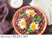 Купить «Bowl of chipotle bean chili with baked eggs», фото № 30631361, снято 23 июля 2017 г. (c) easy Fotostock / Фотобанк Лори