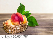 Food, harvest, fresh fruit. Ripe fruit of juicy peach with water drops and leaves in a wicker basket on a wooden background in a rustic style with a copy space. Стоковое фото, фотограф Светлана Евграфова / Фотобанк Лори