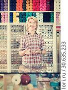 Купить «Mature glad woman seller is ready to help at cash desk», фото № 30635233, снято 24 апреля 2019 г. (c) Яков Филимонов / Фотобанк Лори