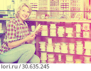 Купить «portrait of female customer standing next to different bands for sewing in shop», фото № 30635245, снято 6 декабря 2019 г. (c) Яков Филимонов / Фотобанк Лори