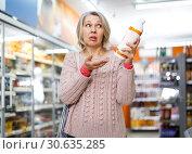 Купить «Shocked casual female reading product label», фото № 30635285, снято 8 февраля 2019 г. (c) Яков Филимонов / Фотобанк Лори