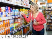 Купить «mature woman choosing food products on shelves», фото № 30635297, снято 8 февраля 2019 г. (c) Яков Филимонов / Фотобанк Лори