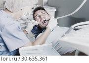 Купить «Young man on dental checkup», фото № 30635361, снято 5 июля 2017 г. (c) Яков Филимонов / Фотобанк Лори