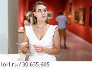 Купить «Woman observing museum exposition», фото № 30635605, снято 28 июля 2018 г. (c) Яков Филимонов / Фотобанк Лори