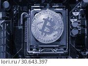 Купить «Silver bitcoin on the microprocessor. Concept of digital cryptocurrency and bitcoin mining», фото № 30643397, снято 4 апреля 2019 г. (c) Зезелина Марина / Фотобанк Лори