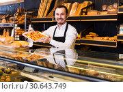 Купить «Confectioner offers a taste of cakes», фото № 30643749, снято 26 января 2017 г. (c) Яков Филимонов / Фотобанк Лори