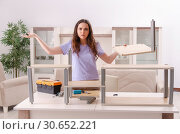 Young woman repairing chair at home. Стоковое фото, фотограф Elnur / Фотобанк Лори
