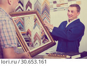 portrait of man seller taking order on picture frame from custom. Стоковое фото, фотограф Яков Филимонов / Фотобанк Лори