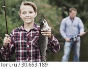 Купить «Fisher boy showing catch fish», фото № 30653189, снято 23 октября 2019 г. (c) Яков Филимонов / Фотобанк Лори