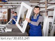 Купить «smiling male professional labours with finished PVC profiles and windows», фото № 30653241, снято 30 марта 2017 г. (c) Яков Филимонов / Фотобанк Лори