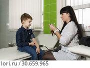 Купить «Медицинский работник готовит стетоскоп для измерения давления мальчику. Ребенок смотрит с интересом», фото № 30659965, снято 17 марта 2019 г. (c) Наталья Гармашева / Фотобанк Лори