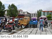 Мотобайки припаркованы на улице в историческом центре Лхасы рядом с пропускным пунктом на главную площадь. Тибет, Китай (2018 год). Редакционное фото, фотограф Овчинникова Ирина / Фотобанк Лори